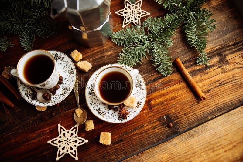 Deux tasses d'expresso avec des morceaux de sucre de canne et de fabricant de café italien sur la table en bois photographie stock
