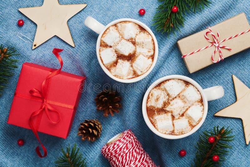 Deux tasses de cacao ou de chocolat chaud avec la guimauve, le boîte-cadeau, le décor de Noël et l'arbre de sapin sur le fond ble photos libres de droits