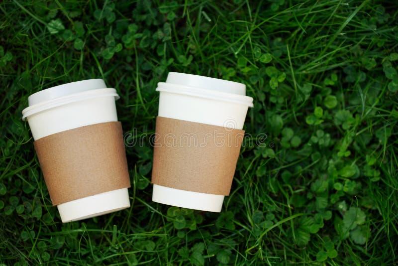 Deux tasses de café à aller sur l'herbe image libre de droits