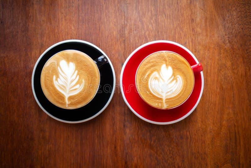Deux tasses de café chaud avec l'art de latte sur la table en bois Boisson préférée de boisson de caffein image stock