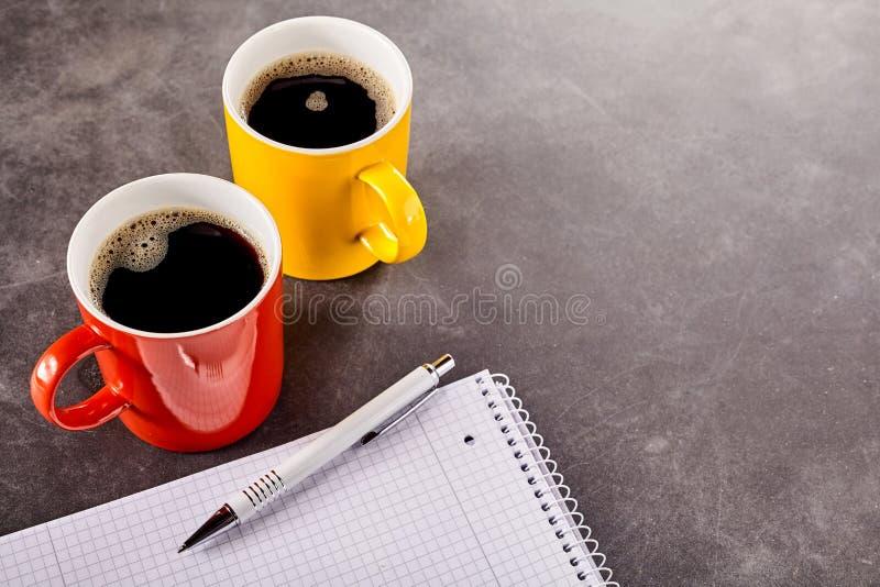 Deux tasses de café près de bloc-notes photos stock