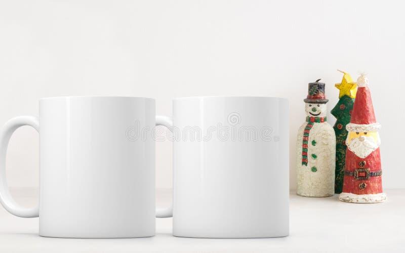 Deux tasses de café vides blanches que la moquerie de thème de Noël s'ajoutent jusqu'à conçoivent ou citent en fonction du client images stock