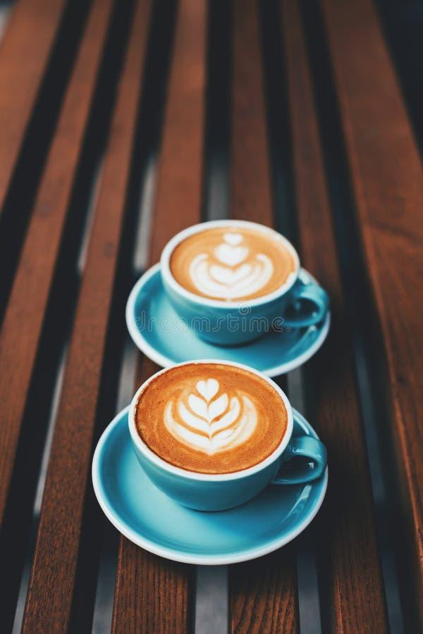 Deux tasses de cappuccino avec l'art de latte photos stock