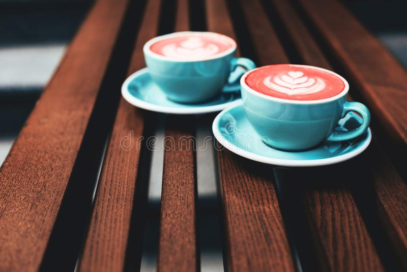 Deux tasses de cappuccino de corail vivant avec l'art de latte images stock