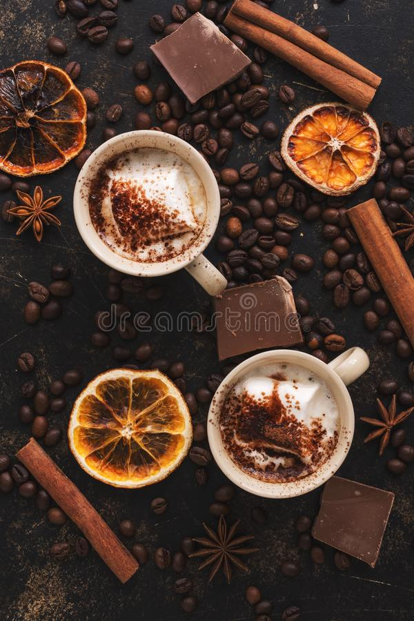 Deux tasses de chocolat chaud avec des guimauves sur un fond rustique décoré des grains de café, de la cannelle et des tranches o photo stock
