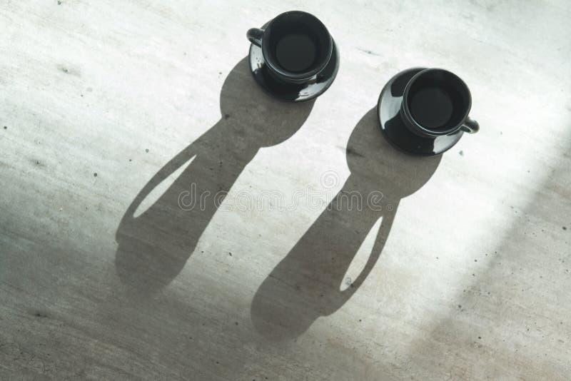 Deux tasses de noir d'argile de café sur la table avec le contre-jour lumineux qui dessine de longues ombres de tasse Café pour d photo stock
