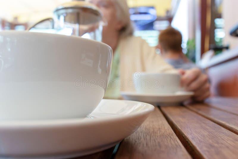 Deux tasses de thé et Français pressent sur la table, femme brouillée derrière photographie stock libre de droits