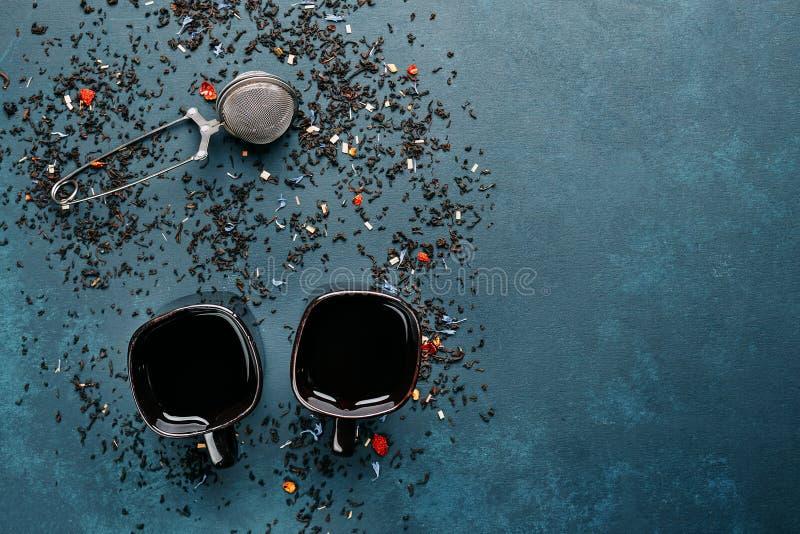 Deux tasses de thé noir avec le teinturier de thé et les feuilles de thé arrosées image libre de droits