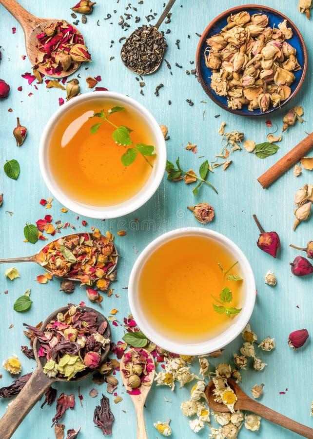 Deux tasses de tisane saine avec la menthe, la cannelle, rose sec et la camomille fleurit dans des cuillères au-dessus de fond bl photos stock
