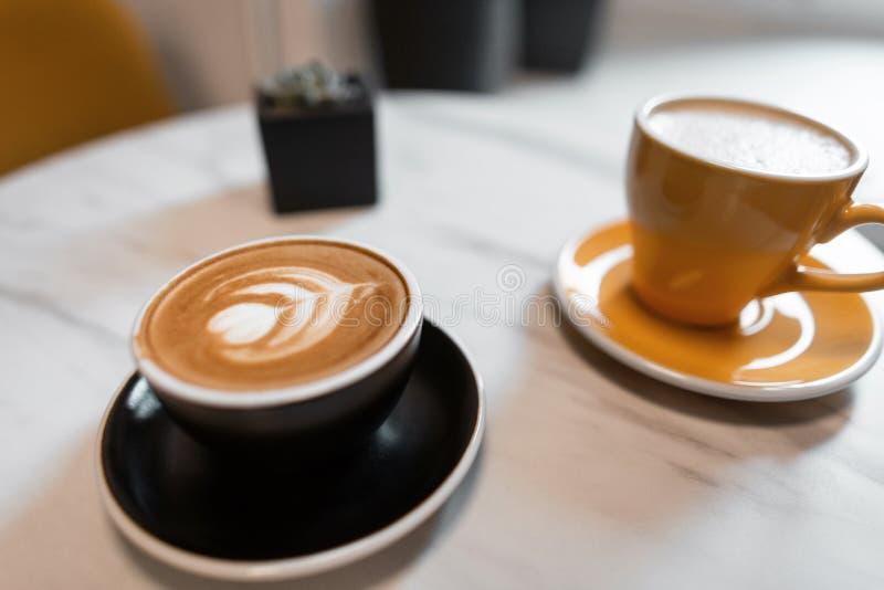 Deux tasses en céramique avec le cappuccino et avec le latte sur une table en bois dans un café Latte avec une belle mousse avec  image libre de droits