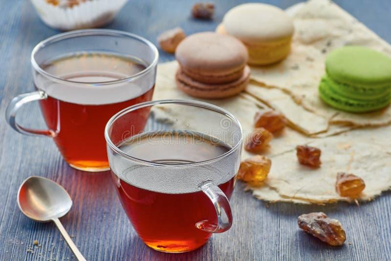 Deux tasses en verre de thé noir et de macarons colorés photo libre de droits