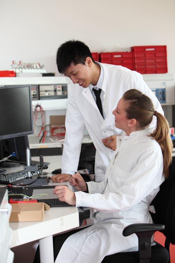 Deux techniciens de laboratoire discutant leur travail image stock