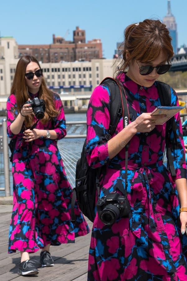 Deux touristes asiatiques de femmes habillant la même manière marchant au bord de mer d'abruti photographie stock libre de droits