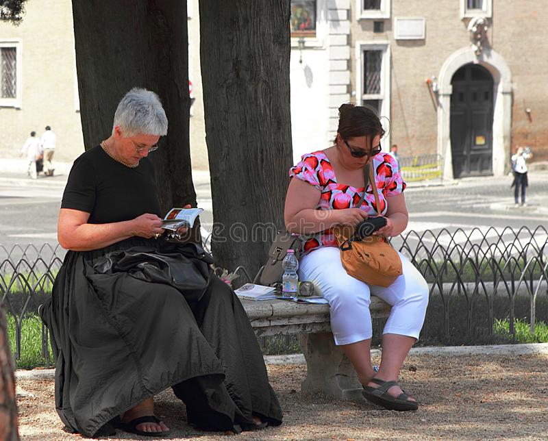 Deux touristes féminins faisant une pause sur un banc à Rome photo stock