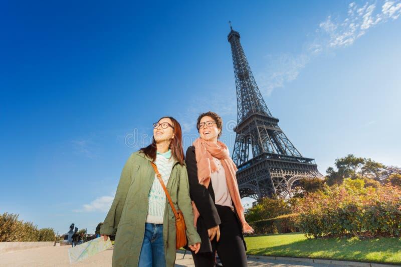 Deux touristes féminins marchant près de Tour Eiffel photo stock