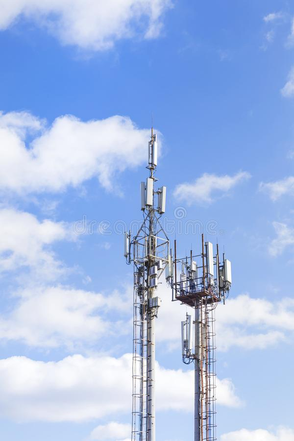 Deux tours de cellules contre le ciel bleu avec des nuages Communi mobile image libre de droits