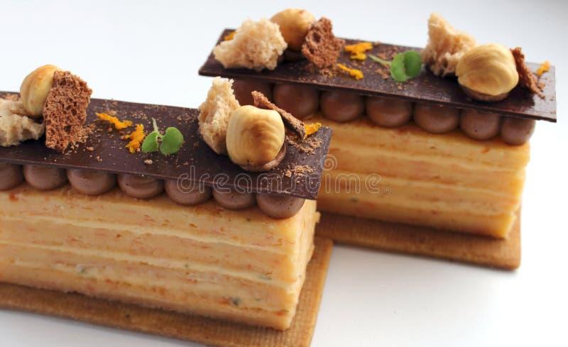 Deux tranches oranges de gâteau d'opéra avec des noisettes et ganache sur la base de biscuit d'isolement sur le fond blanc photo libre de droits