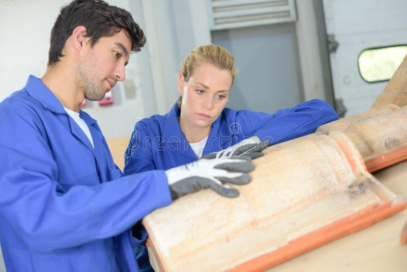 Deux travailleurs apprenant à couvrir de tuiles des maisons photographie stock