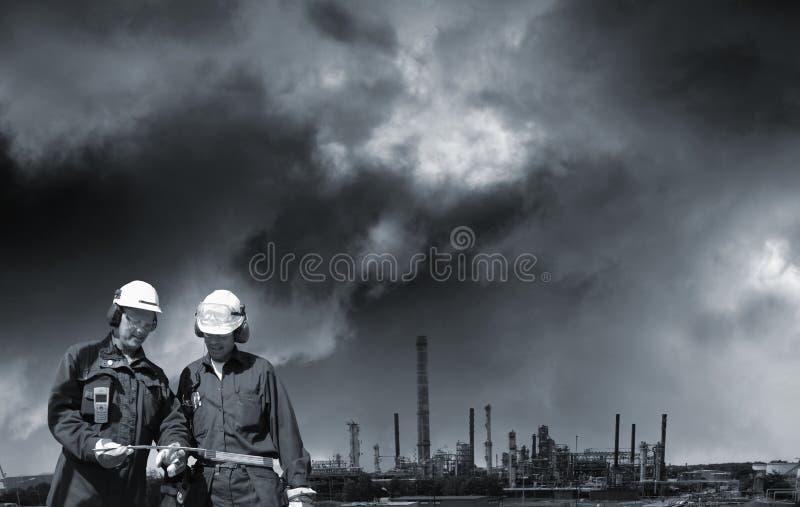 Deux travailleurs d'industrie et raffinerie de pétrole éloigné photo libre de droits