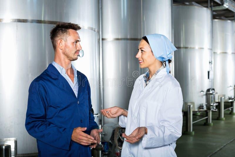 Deux travailleurs dans l'uniforme protecteur parlant dans la section secondaire de fermentation images libres de droits