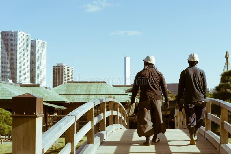 Deux travailleurs de la construction japonais croisant un pont dans des jardins de Hamarikyu, Tokyo, Japon photographie stock