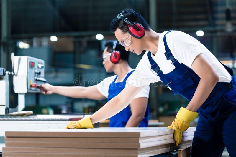 Deux travailleurs en bois dans des planches à découper de menuiserie photos stock