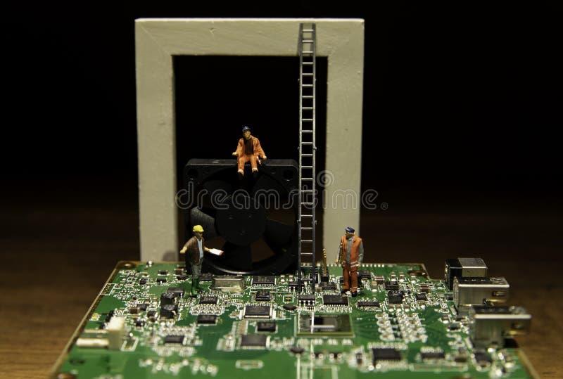 Deux travailleurs et un agent de maîtrise travaillant au conseil principal d'ordinateur et au fan noir images stock