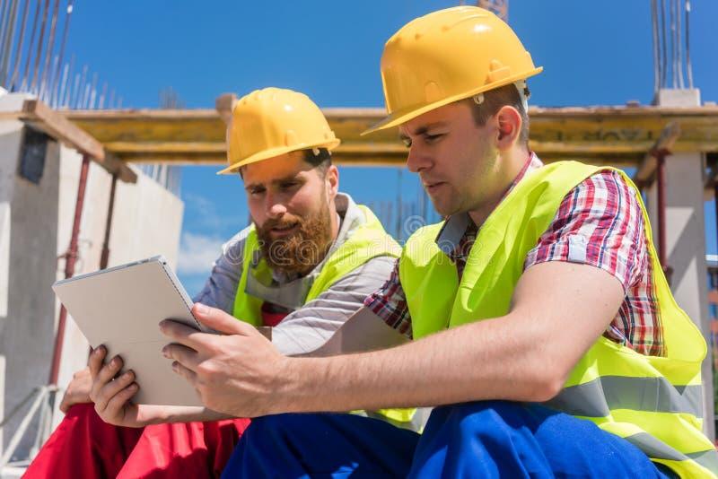 Deux travailleurs lisant la documentation en ligne ou observant une vidéo pendant la coupure photographie stock