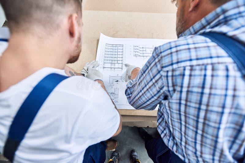 Deux travailleurs regardant des plans photo stock