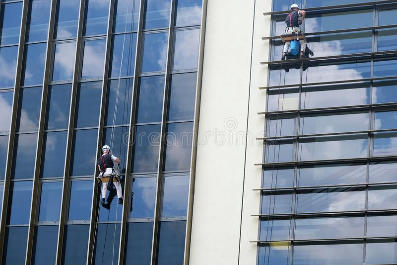 Deux travailleurs s'élevants nettoyant le mur de verre extérieur d'un bâtiment images libres de droits