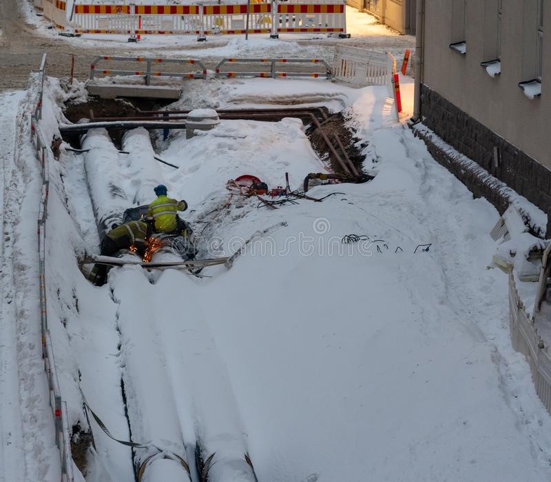 Deux travailleurs soudant sur un grand tuyau parmi la neige dans un chantier de construction urbain, Helsinki Finlande images libres de droits