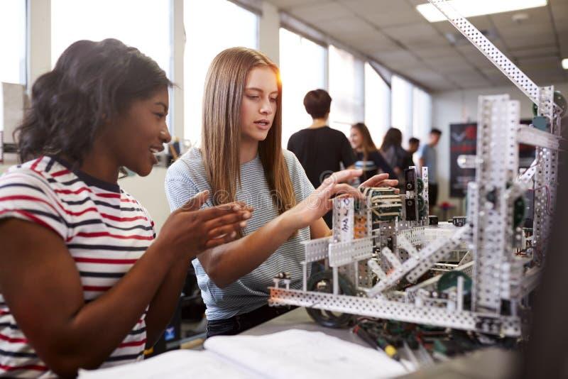 Deux ?tudiants universitaires f?minins construisant la machine en robotique de la Science ou machinant la classe photographie stock libre de droits