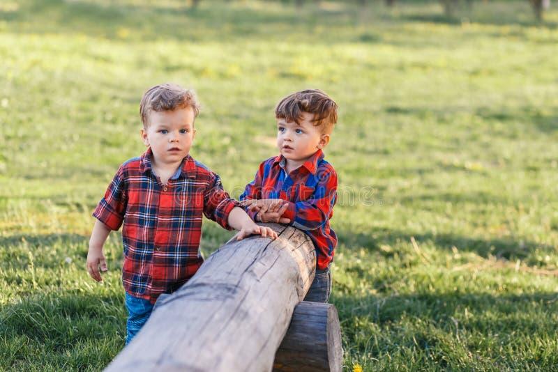 Deux tweens mignons de garçons de frère ayant l'amusement dehors au coucher du soleil dans le pays images libres de droits