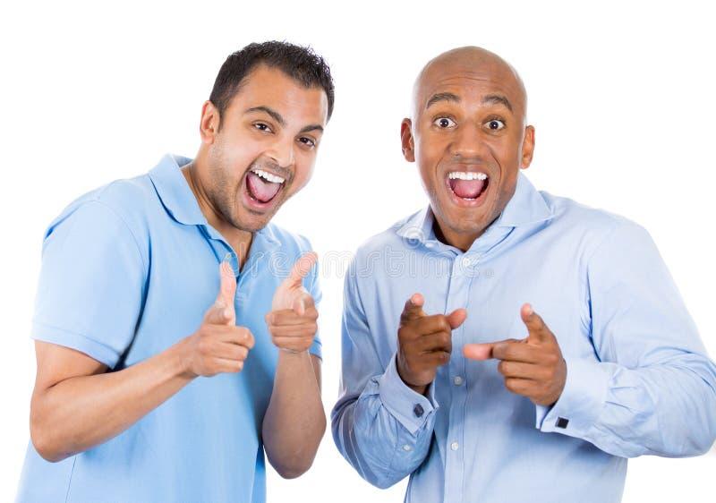 deux types frais dirigeant des doigts à vous font des gestes et sourire photo stock