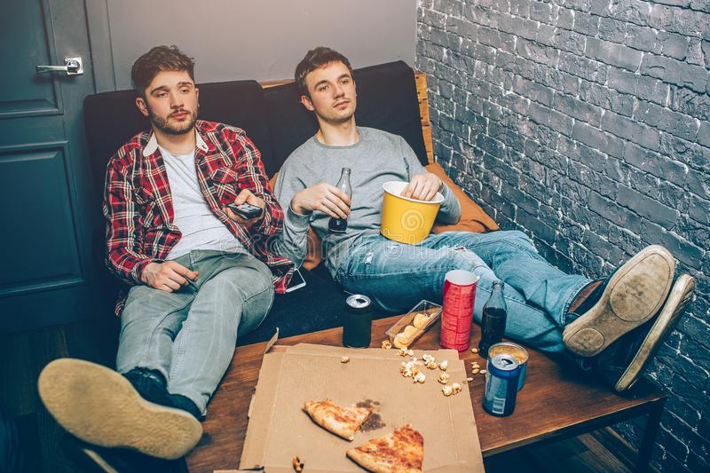 Deux types s'asseyant sur le divan et tenant de la nourriture et boissons dans leurs mains Ils se sentent décontractés et fatigué images libres de droits