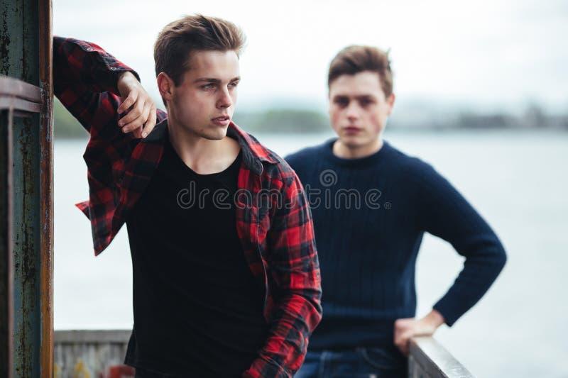 Deux types se tiennent dans un bâtiment abandonné sur le lac photos libres de droits