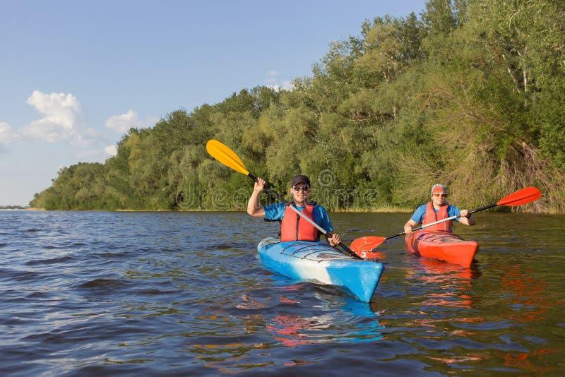 Deux types voyagent la rivière sur kayaking photo libre de droits