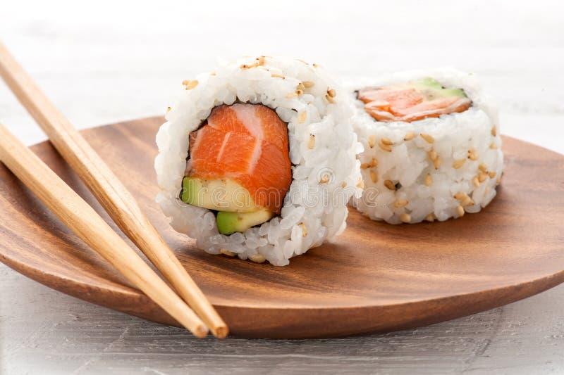 Deux uramaki frais de sushi de saumons et d'avocat photos stock