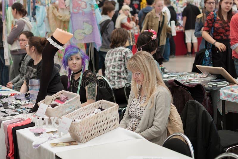 Deux vendeuses aux marchés avec des accessoires d'habillement chez Animefest image stock