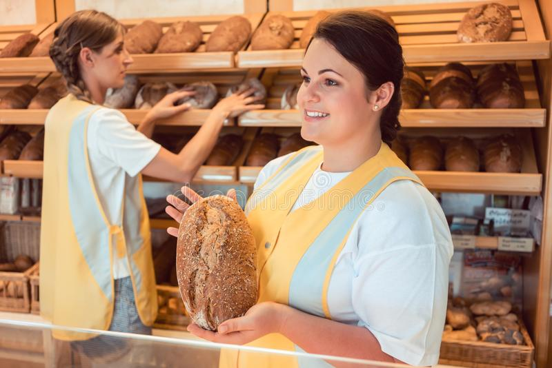 Deux vendeuses vendant le pain et d'autres produits dans la boulangerie font des emplettes photos libres de droits