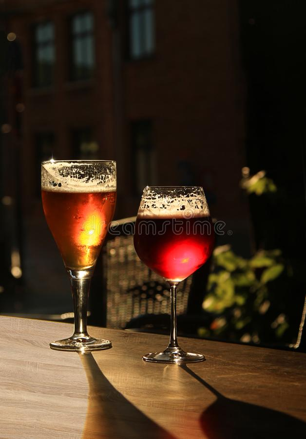 Deux verres avec de la bière froide et le cidre sur la table en bois de café Fond foncé de tache floue avec l'espace de copie photo libre de droits