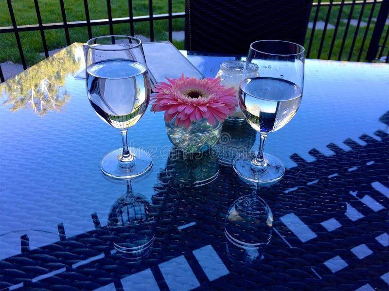 Deux verres avec l'eau et une fleur sur le Tableau photographie stock libre de droits