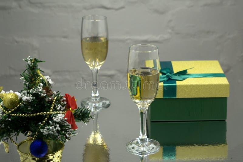 Deux verres avec le champange, branche d'arbre de sapin avec la décoration, boîte-cadeau sur un fond noir avec les lightes multic photographie stock