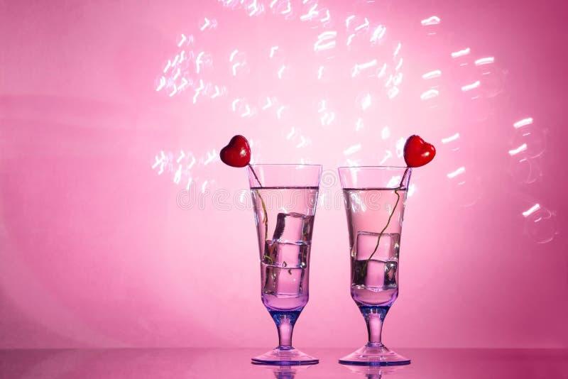 Deux verres avec un cocktail et deux coeurs, concept de Saint-Valentin photo stock