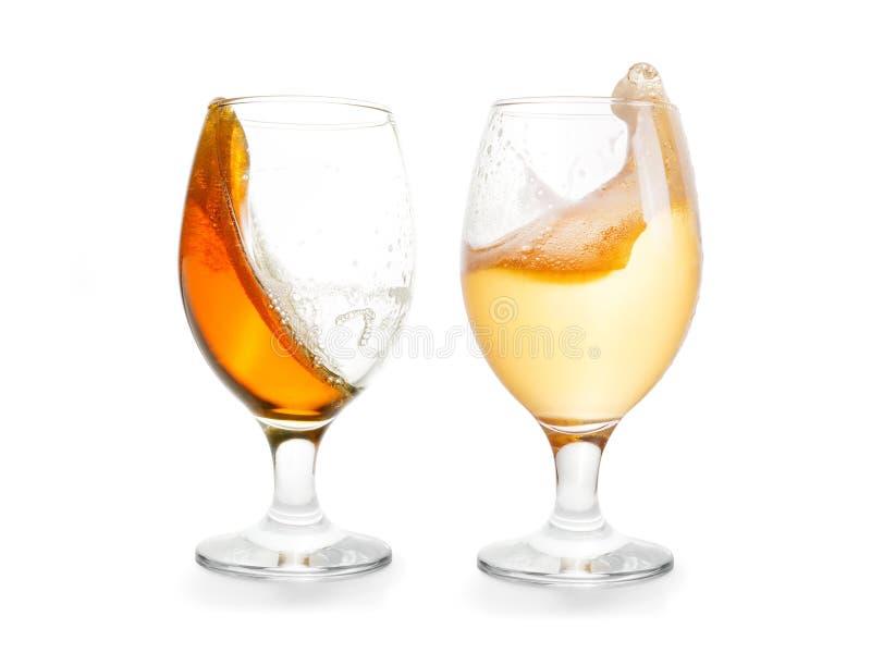 Deux verres d'éclabousser la bière Foncé et lumière un D'isolement avec photos stock