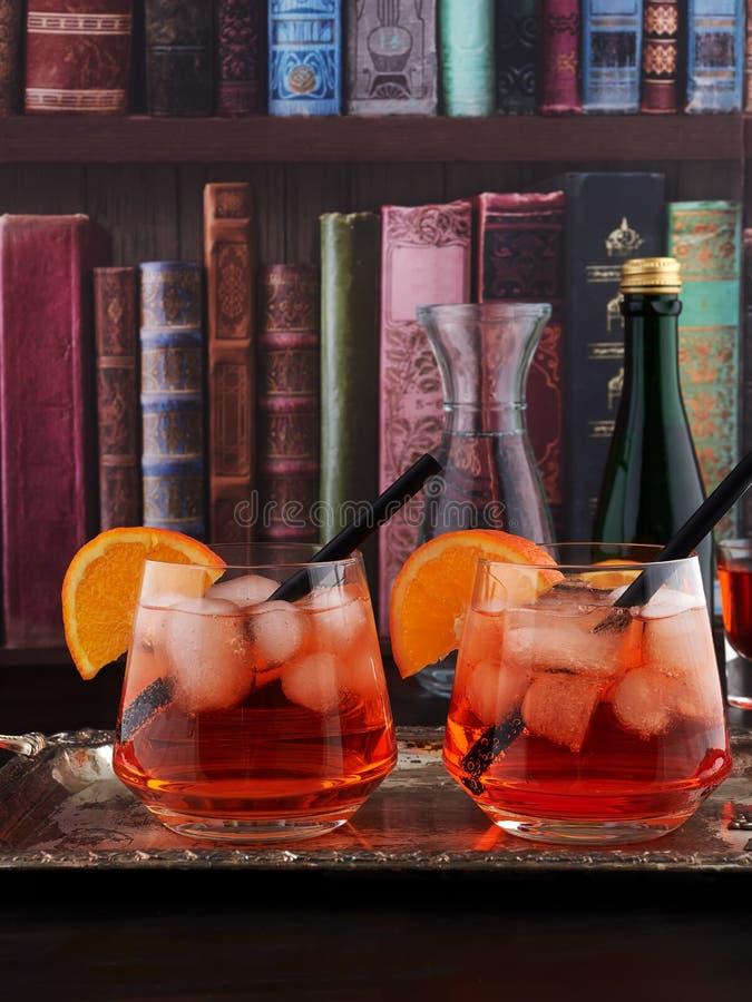 Deux verres d'Aperol Spritz l'ensemble sur un plateau argenté, avec un fond de papier peint d'étagère image libre de droits