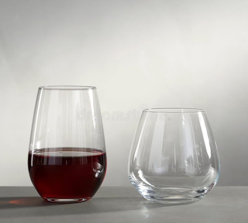 Deux verres d'eau-de-vie fine vides et avec de l'alcool d'isolement sur le fond gris image stock