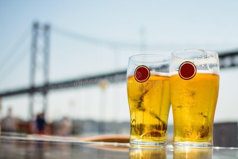 Deux verres de bière blonde sur le fond du pont suspendu images stock