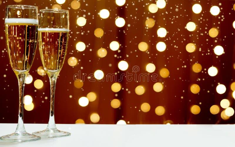 Deux verres de champagne écumant sur le fond des guirlandes de fête, la neige blanche tombe photos stock