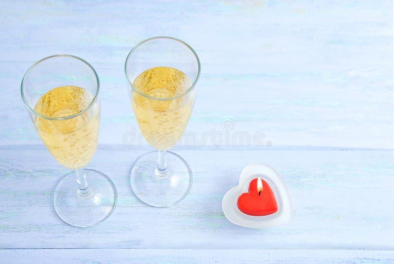 Deux verres de champagne de scintillement et d'une bougie en forme de coeur rouge images libres de droits